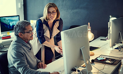 Buy stock photo Shot of two businesspeople working late in an office