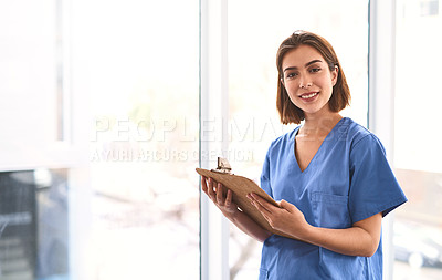 Buy stock photo Portrait of a cheerful young female doctor holding a clipboard while looking at the camera in a clinic