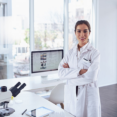 Buy stock photo Portrait of a confident young female scientist standing with arms folded while looking at the camera in a laboratory
