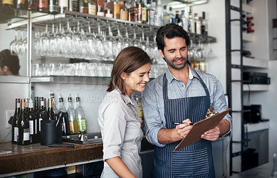 Buy stock photo Cropped shot of two young entrepreneurs looking at a clipboard while working in their coffee shop
