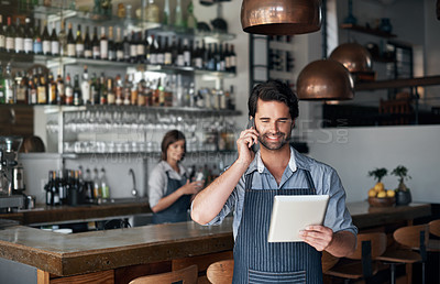 Buy stock photo Cropped shot of a handsome young man using a tablet and cellphone while standing in his coffee shop