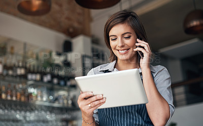 Buy stock photo Cropped shot of an attractive young woman using a tablet and cellphone while standing in her coffee shop