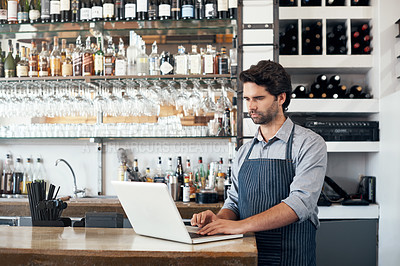 Buy stock photo Cropped shot of a handsome young man working on a laptop while standing in his coffee shop