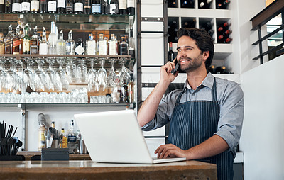 Buy stock photo Cropped shot of a handsome young man using a laptop and cellphone while standing in his coffee shop