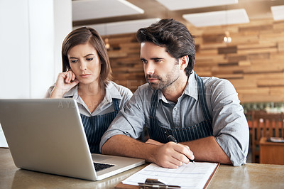 Buy stock photo Cropped shot of two young entrepreneurs working on a laptop in their office