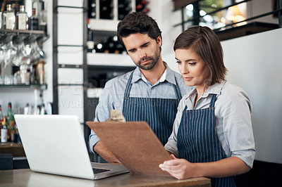 Buy stock photo Cropped shot of two young entrepreneurs looking at a clipboard while working on a laptop in their coffee shop