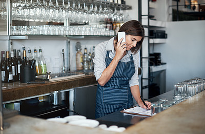 Buy stock photo Cropped shot of an attractive young woman using a cellphone while working in her coffee shop
