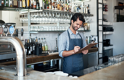 Buy stock photo Cropped shot of a handsome young man using a clipboard while working in his coffee shop