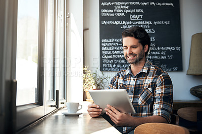 Buy stock photo Cropped shot of a handsome young man using his tablet while sitting in a coffee shop