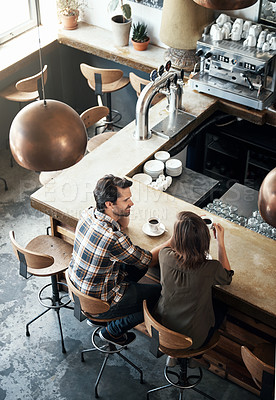 Buy stock photo High angle shot of a young couple enjoying a cup of coffee while sitting in a coffee shop