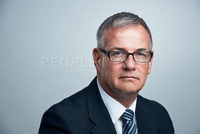 Buy stock photo Studio shot of a mature businessman posing against a grey background