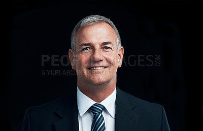 Buy stock photo Studio shot of a mature businessman posing against a dark background