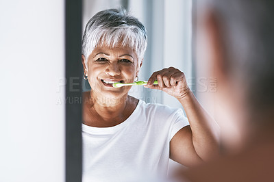 Buy stock photo Portrait of a cheerful mature woman brushing her teeth while looking into a mirror at home