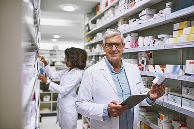Buy stock photo Portrait of a cheerful mature male pharmacist holding a digital tablet and box of meds while looking at the camera