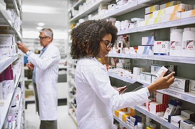 Buy stock photo Shot of two focused pharmacist walking around and doing stock inside of a pharmacy