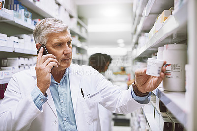 Buy stock photo Shot of a focused mature male pharmacist talking on his cellphone while reading the back of a medication box