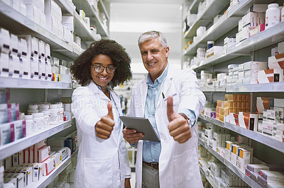 Buy stock photo Portrait of two cheerful pharmacists holding a digital tablet and showing thumbs up while looking at the camera