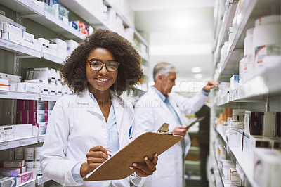 Buy stock photo Portrait of a cheerful young female pharmacist holding a clipboard and doing stock while looking at the camera