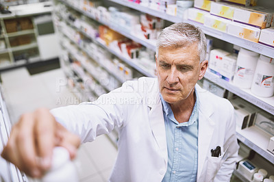 Buy stock photo Shot of a focused mature male pharmacist putting a medication bottle back on the shelf in a pharmacy