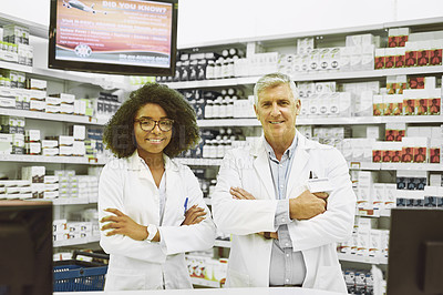 Buy stock photo Portrait of two cheerful and confident pharmacist standing with arms folded while looking into the camera in a pharmacy