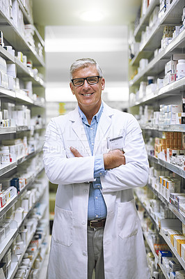 Buy stock photo Portrait of a cheerful mature male pharmacist standing with his arms folded while looking at the camera in a pharmacy