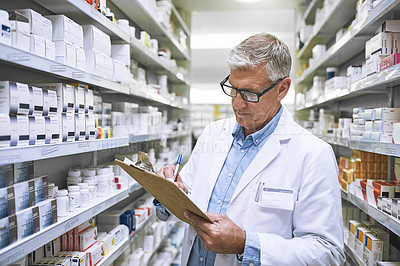 Buy stock photo Shot of a focused mature male pharmacist making notes of the medication stock on the shelves in a pharmacy
