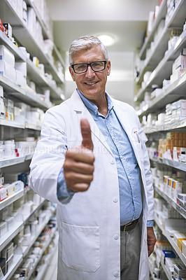 Buy stock photo Portrait of a cheerful mature male pharmacist showing thumbs up while looking at the camera in a pharmacy