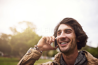 Buy stock photo Shot of a cheerful young man talking on his phone while standing outside in a park