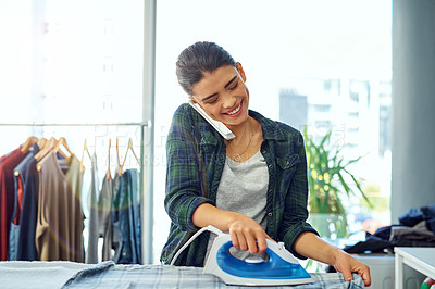 Buy stock photo Cropped shot of an attractive young woman using her cellphone while doing the ironing at home