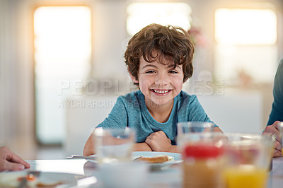 Buy stock photo Cropped portrait of an adorable little boy eating breakfast while sitting at the dining room table