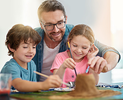Buy stock photo Cropped shot of a handsome man and his two kids building a volcano for school