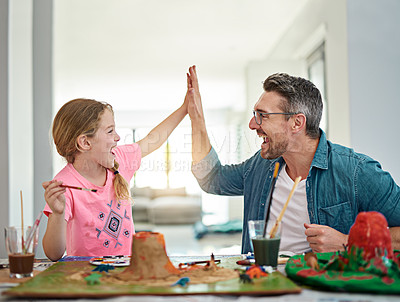 Buy stock photo Cropped shot of a handsome man and his daughter high fiving while building a volcano for school