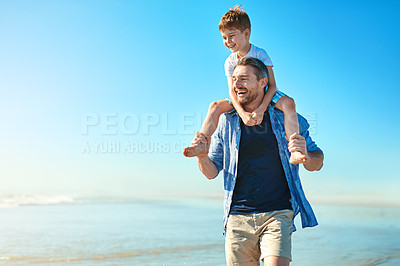 Buy stock photo Shot of a father and his little son enjoying some quality time together at the beach
