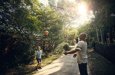 Buy stock photo Shot of a father and his son playing ball outside