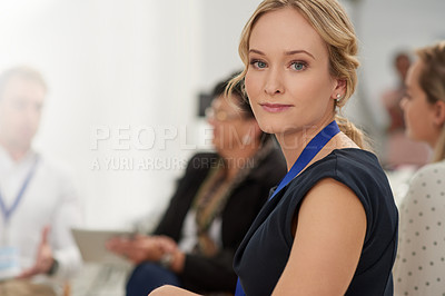Buy stock photo Portrait of a confident young businesswoman sitting down in a boardroom with colleagues during a presentation
