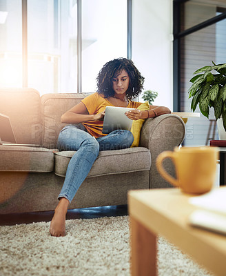 Buy stock photo Full length shot of an attractive young woman using her tablet while relaxing at home on the weekend