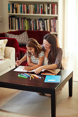 Buy stock photo Shot of a beautiful mother helping her adorable daughter with her homework at home