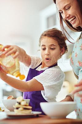 Buy stock photo Shot of a mother and daughter preparing food in the kitchen at home