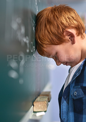 Buy stock photo Cropped shot of an elementary school boy pressing his head against the blackboard with frustration in class