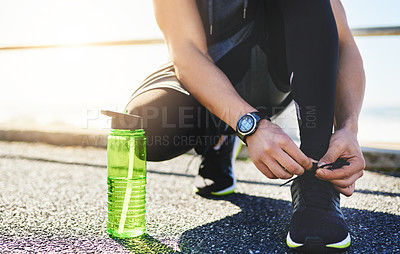 Buy stock photo Closeup shot of an unidentifiable man tying his laces while exercising outdoors