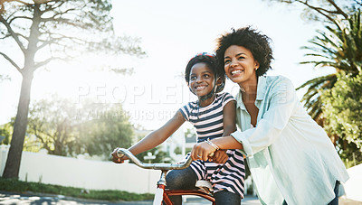 Buy stock photo Shot of a cheerful young father helping his son to ride his bike outside during the day