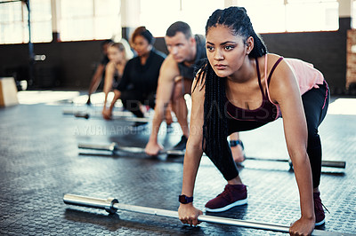 Buy stock photo Shot of a fitness group using steel bars in their session at the gym