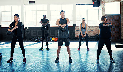 Buy stock photo Shot of a fitness group using kettle-bells in their session at the gym