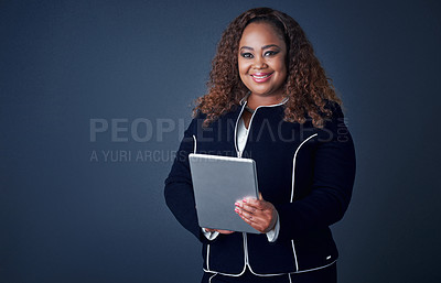 Buy stock photo Portrait of a confident young businesswoman working on her digital tablet while standing against a blue background