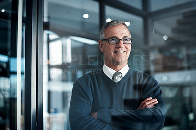 Buy stock photo Shot of a mature businessman looking thoughtful while working late in an office
