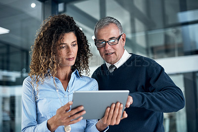 Buy stock photo Shot of two businesspeople working late on a digital tablet in an office