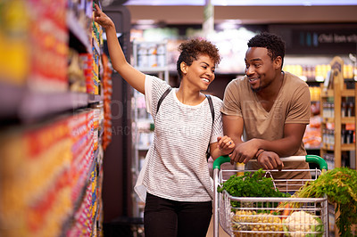 Buy stock photo Shot of a young couple shopping in a grocery store