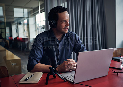 Buy stock photo Shot of a mature man recording a podcast on a laptop in a modern office