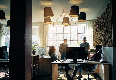 Buy stock photo Shot of a group of colleagues having a discussion in a modern office