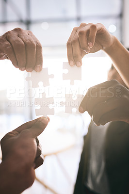Buy stock photo Shot of a motivated group of unrecognizable businesspeople each holding a puzzle piece next to each other